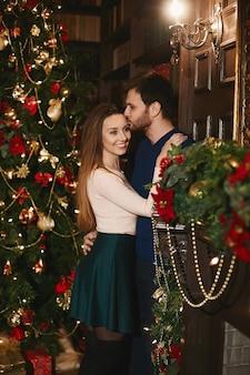 Jeune bel homme embrassant et embrassant une femme modèle magnifique à l'intérieur décoré pour noël