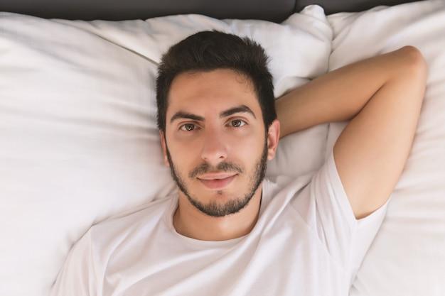 Jeune bel homme endormi dans son lit.