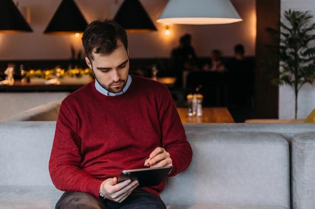 Un jeune bel homme est assis dans un café et se penche sur un gadget