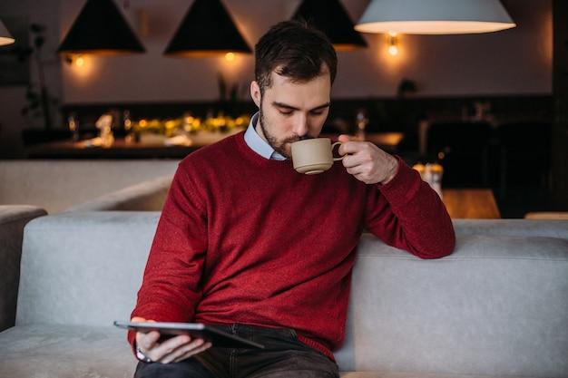 Jeune bel homme est assis dans un café avec une tasse de café et regarde gadget
