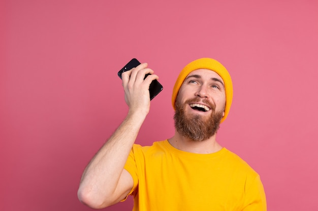 Jeune bel homme européen souriant heureux écoute message audio à l'aide de smartphone sur rose