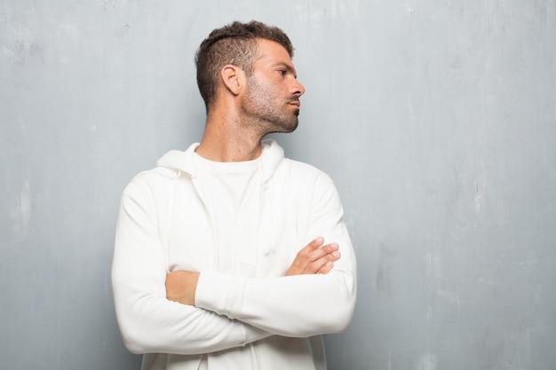 Jeune bel homme avec une expression dissidente, grave, sévère, les bras croisés dans la désapprobation.