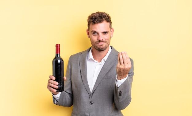 Jeune bel homme faisant un geste de capice ou d'argent, vous disant de payer. concept de bouteille de vin