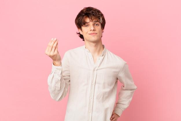 Jeune bel homme faisant un geste de capice ou d'argent, vous disant de payer