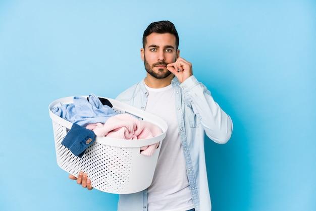 Jeune bel homme faisant la lessive isolé avec les doigts sur les lèvres gardant un secret.