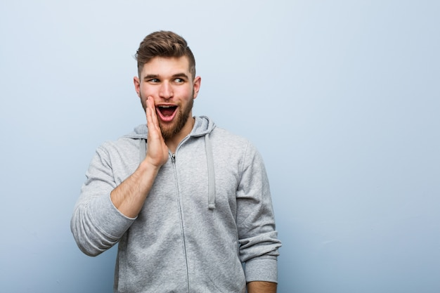 Jeune bel homme de fitness dit un secret secret des nouvelles de freinage et regarde de côté