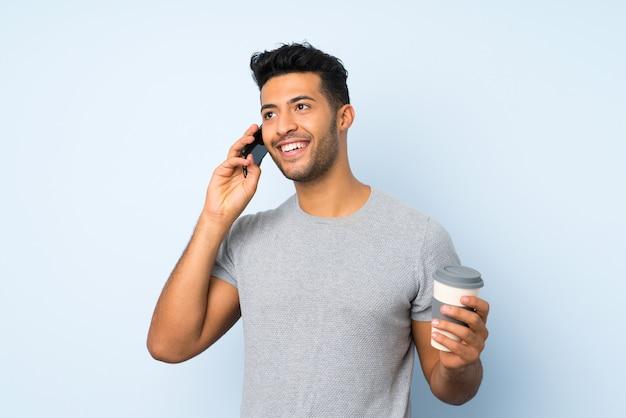 Jeune bel homme sur fond isolé tenant un café à emporter et un mobile
