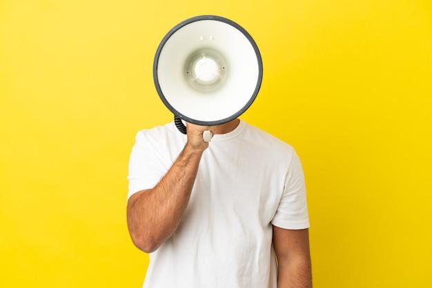 Jeune bel homme sur fond jaune isolé criant à travers un mégaphone pour annoncer quelque chose