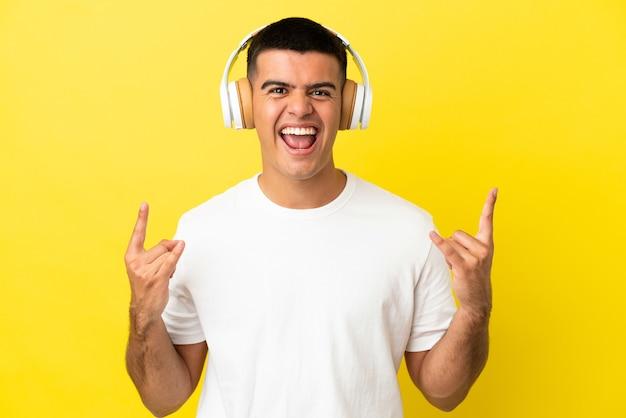 Jeune bel homme sur fond jaune isolé écoutant de la musique faisant un geste rock
