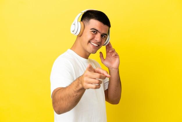 Jeune bel homme sur fond jaune isolé écoutant de la musique et pointant vers l'avant