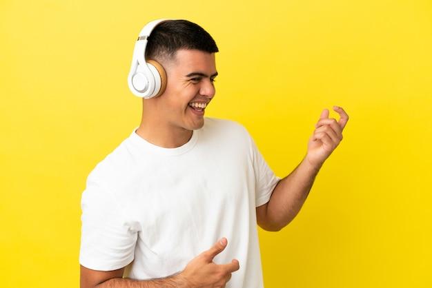 Jeune bel homme sur fond jaune isolé, écouter de la musique et faire un geste de guitare