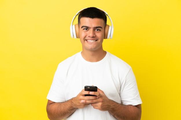 Jeune bel homme sur fond jaune isolé, écouter de la musique avec un mobile et à l'avant