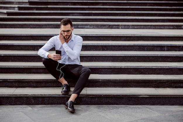 Jeune bel homme geek élégamment habillé assis sur les escaliers à l'extérieur et écouter de la musique sur un téléphone intelligent.