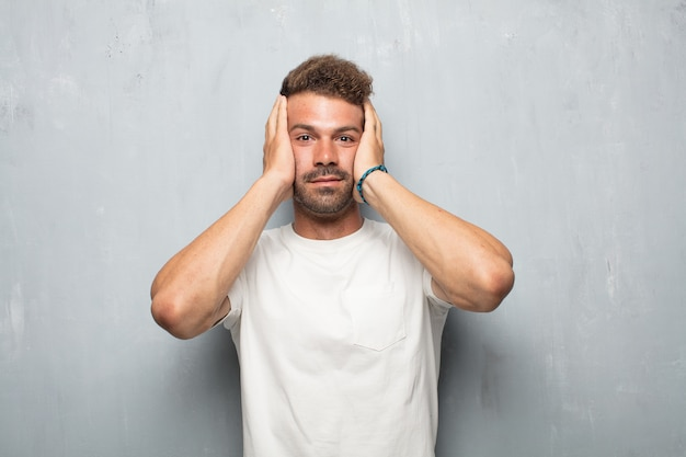 Jeune bel homme avec un geste stressé, avec les deux mains serrées couvrant à moitié le visage.