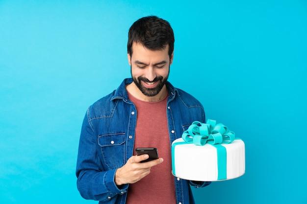 Jeune bel homme avec un gros gâteau sur bleu en envoyant un message avec le mobile