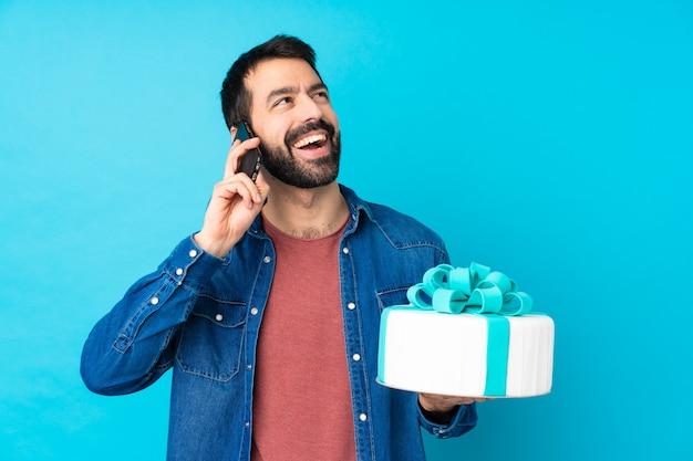 Jeune bel homme avec un gros gâteau en gardant une conversation avec le téléphone mobile