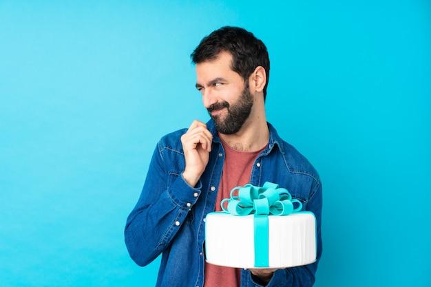Jeune bel homme avec un gros gâteau sur un mur bleu isolé complotant quelque chose
