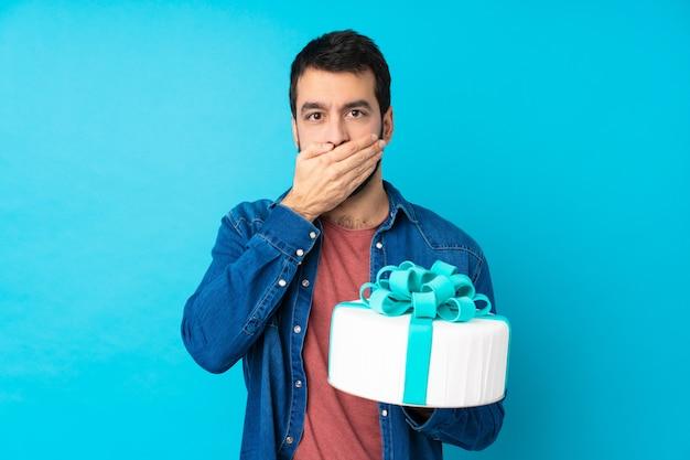 Jeune bel homme avec un gros gâteau sur un mur bleu isolé couvrant la bouche avec les mains