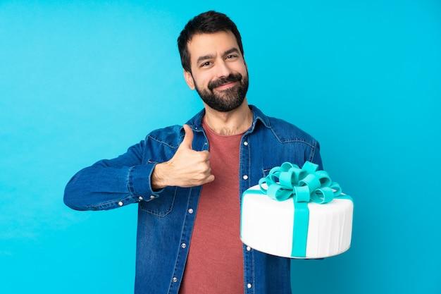 Jeune bel homme avec un gros gâteau sur un mur bleu isolé donnant un coup de pouce geste