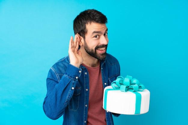 Jeune bel homme avec un gros gâteau sur un mur bleu isolé écouter quelque chose en mettant la main sur l'oreille