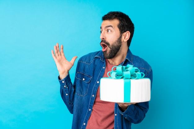 Jeune bel homme avec un gros gâteau sur un mur bleu isolé avec une expression faciale surprise