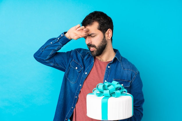 Jeune bel homme avec un gros gâteau sur un mur bleu isolé avec une expression fatiguée et malade