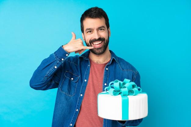 Jeune bel homme avec un gros gâteau sur un mur bleu isolé faisant un geste de téléphone. rappelez-moi signe