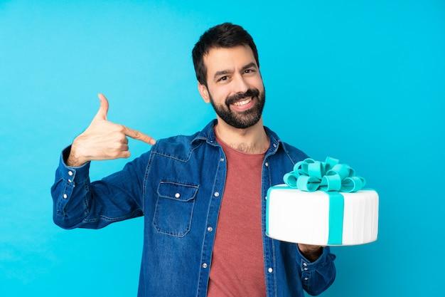 Jeune bel homme avec un gros gâteau sur le mur bleu isolé, fier et satisfait de lui-même