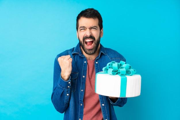 Jeune bel homme avec un gros gâteau sur un mur bleu isolé frustré par une mauvaise situation