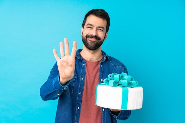 Jeune bel homme avec un gros gâteau sur le mur bleu isolé heureux et comptant quatre avec les doigts