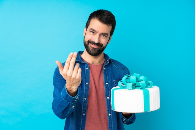 Jeune bel homme avec un gros gâteau sur un mur bleu isolé invitant à venir avec la main. heureux que tu sois venu