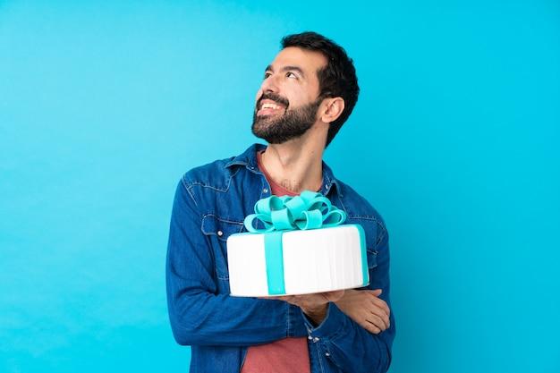 Jeune bel homme avec un gros gâteau sur un mur bleu isolé en levant tout en souriant