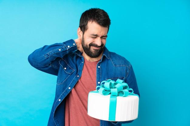 Jeune bel homme avec un gros gâteau sur un mur bleu isolé avec des maux de cou