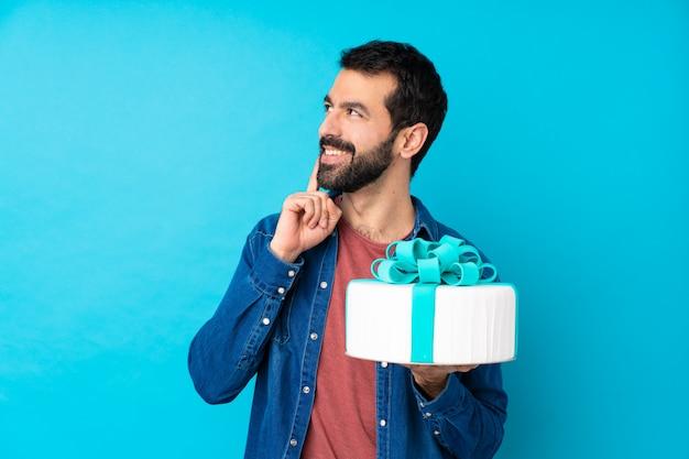 Jeune bel homme avec un gros gâteau sur le mur bleu isolé en pensant à une idée tout en levant
