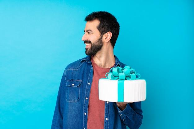 Jeune bel homme avec un gros gâteau sur le mur bleu isolé à la recherche de côté