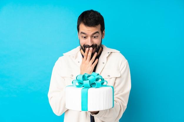 Jeune bel homme avec un gros gâteau sur le mur bleu isolé