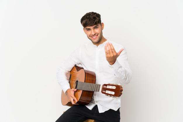Jeune bel homme avec guitare sur blanc isolé invitant à venir avec la main. heureux que tu sois venu