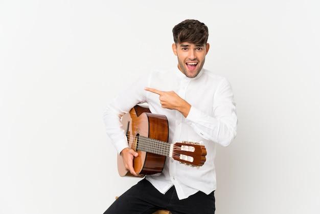 Jeune bel homme avec guitare sur mur blanc isolé surpris et pointant le côté