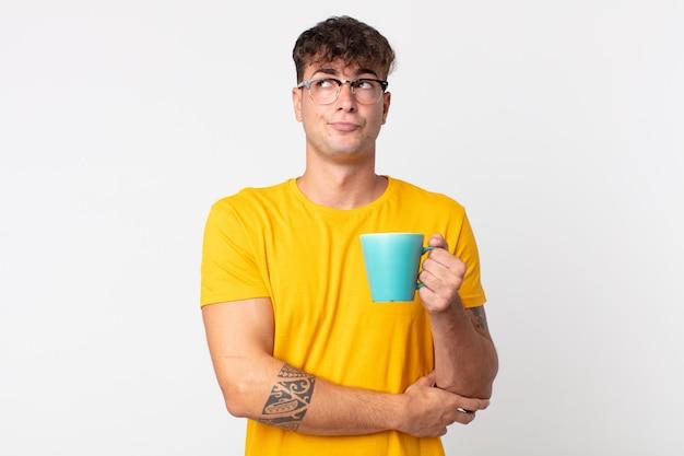 Jeune bel homme haussant les épaules, se sentant confus et incertain et tenant une tasse de café