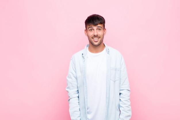 Jeune bel homme heureux et agréablement surpris, excité par une expression fascinée et choquée sur le mur rose