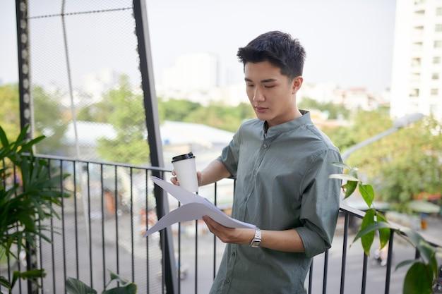 Jeune bel homme heureux assis et lisant un livre, buvant une boisson sur le balcon extérieur