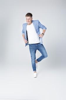 Jeune bel homme heureux en jeans et veste sautant