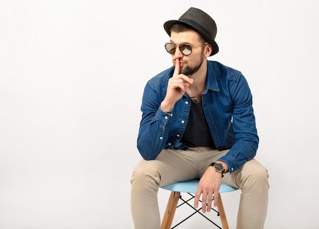 Jeune bel homme hipster, fond de studio blanc isolé, tenue élégante, chemise en jean, pantalon, chapeau, lunettes de soleil, assis sur une chaise, doigt sur les lèvres, geste de silence, expression, émotion