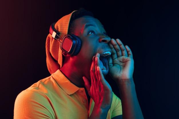 Le jeune bel homme hipster heureux écoute de la musique avec des écouteurs au noir avec des néons