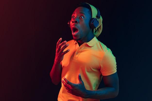Le jeune bel homme hipster heureux écoute de la musique avec des écouteurs au studio noir avec des néons. discothèque, boîte de nuit, style hip hop, émotions positives, expression du visage, concept de danse