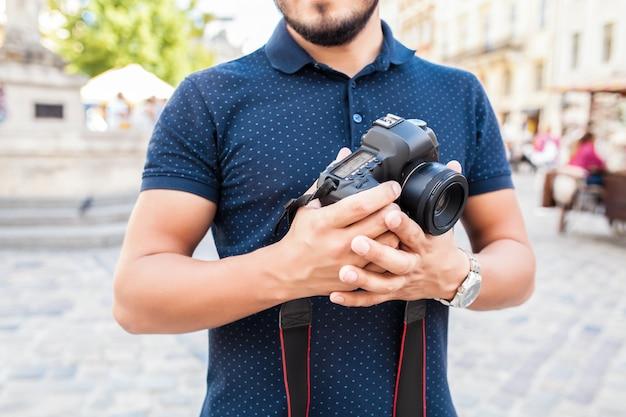 Jeune bel homme hipster marchant avec appareil photo sur la rue de la vieille ville