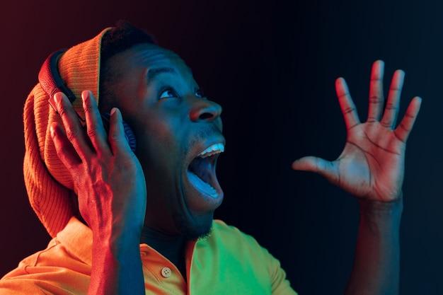 Le jeune bel homme hipster surpris heureux écoute de la musique avec des écouteurs au noir avec des néons
