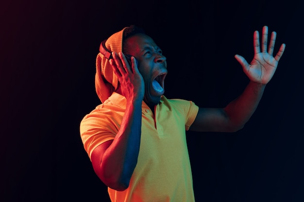 Le jeune bel homme hipster surpris heureux écoute de la musique avec des écouteurs au studio noir avec néons. discothèque, boîte de nuit, style hip hop, émotions positives, expression du visage, concept de danse