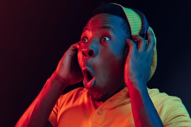 Le jeune bel homme hipster surpris heureux écoute de la musique