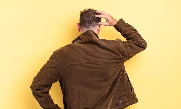 Jeune bel homme hispanique se sentant désemparé et confus, pensant à une solution, avec la main sur la hanche et l'autre sur la tête, vue arrière